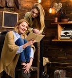 Девушки с жизнерадостными сторонами смеясь над о смешном моменте в книге Мама и дочь читая совместно на холодном вечере зимы Стоковое фото RF