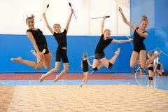 Девушки с индийскими клубами во время высокого прыжка Стоковая Фотография
