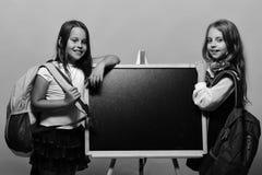 Девушки с каверзными усмехаясь сторонами и свободными волосами Школьницы рядом с доской на розовой предпосылке Стоковое фото RF