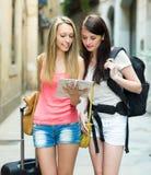 Девушки с картой чтения багажа Стоковое Фото