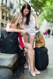 Девушки с картой чтения багажа Стоковые Фото