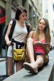 Девушки с картой чтения багажа Стоковые Фотографии RF