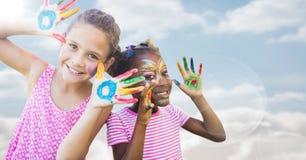 Девушки с краской на руках против неба с пирофакелом Стоковое Изображение RF