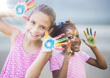 Девушки с краской на руках против расплывчатого пляжа с пирофакелом Стоковые Фотографии RF