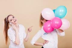 2 девушки с мобильным телефоном и воздушными шарами Стоковая Фотография RF
