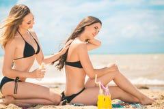 Девушки с лосьоном suntan на пляже Стоковое Изображение
