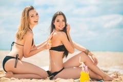 Девушки с лосьоном suntan на пляже Стоковая Фотография