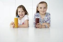 Девушки с пить апельсина и шоколада на таблице Стоковые Изображения