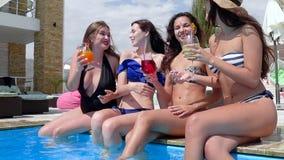Девушки с покрашенными ногами напитка развевая в голубом poolside и связывают друг с другом видеоматериал