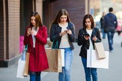 Девушки с посланием бумажных сумок на умных телефонах стоковые фото