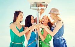 Девушки с стеклами шампанского на шлюпке Стоковое Изображение