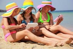 Девушки с таблеткой на пляже Стоковые Изображения