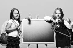 Девушки с усмехаясь сторонами и большими пальцами руки вверх задняя школа к Стоковое Изображение RF