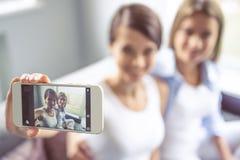 Девушки с устройством Стоковая Фотография