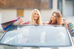 Девушки с хозяйственными сумками в автомобиле с откидным верхом Стоковые Фотографии RF