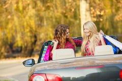 Девушки с хозяйственными сумками в автомобиле с откидным верхом Стоковое Изображение
