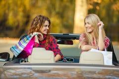 Девушки с хозяйственными сумками в автомобиле с откидным верхом Стоковые Фото
