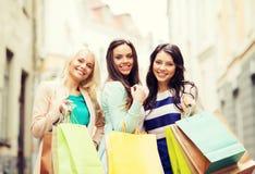Девушки с хозяйственными сумками в городе Стоковые Фото
