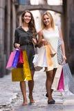 Девушки с хозяйственными сумками на улице Стоковые Изображения