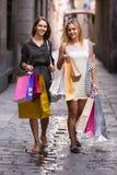 Девушки с хозяйственными сумками на улице Стоковое фото RF