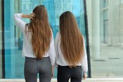 2 девушки с худенькой диаграммой стоят с их задними частями к ca Стоковая Фотография