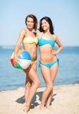 Девушки с шариком на пляже Стоковые Фото