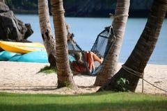 Девушки туристов ослабляя и лежа на гамаке на пляже Стоковое Изображение