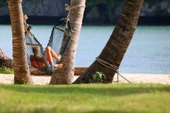 Девушки туристов ослабляя и лежа на гамаке на пляже Стоковые Изображения