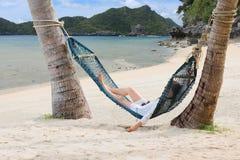 Девушки туристов ослабляя и лежа на гамаке на пляже Стоковая Фотография RF