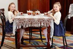Девушки дублируют выпивая чай на античной таблице с tablecl шнурка Стоковое Изображение RF