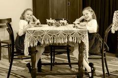 Девушки дублируют выпивая чай на античной таблице с tablecl шнурка Стоковые Изображения