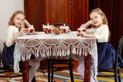 Девушки дублируют выпивая чай на античной таблице с tablecl шнурка Стоковая Фотография RF