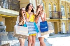 Девушки увидели новый магазин Девушки держа хозяйственные сумки и aro прогулки Стоковое Изображение