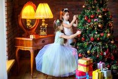Девушки украшают праздничную рождественскую елку Стоковые Фото