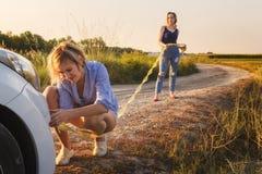 2 девушки улавливают веревочку кудели на сломленном автомобиле на сельской дороге в лучах захода солнца стоковая фотография