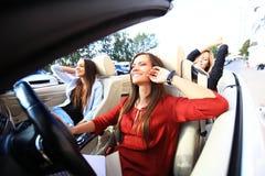 3 девушки управляя в обратимом автомобиле и имея потеху Стоковые Изображения
