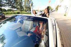 3 девушки управляя в обратимом автомобиле и имея потеху Стоковое Изображение RF