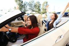 3 девушки управляя в обратимом автомобиле и имея потеху Стоковое Фото