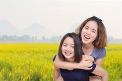 Девушки усмехаясь в поле цветка Стоковые Фото