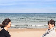 Девушки усмехаясь и смотря один другого на пляже Стоковые Фотографии RF