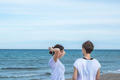 Девушки усмехаясь на пляже и вытягивая их заднюю часть волос с нормальной ориентацией Стоковые Фотографии RF
