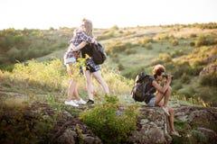 Девушки усмехаясь, обнимающ, сидящ на утесе, наслаждаясь взглядом в каньоне Стоковое Фото