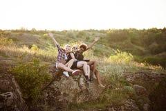 Девушки усмехаясь, сидящ на утесе, наслаждаясь взглядом в каньоне Стоковое Фото