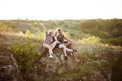 Девушки усмехаясь, сидящ на утесе, наслаждаясь взглядом в каньоне Стоковое Изображение