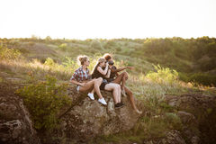Девушки усмехаясь, сидящ на утесе, наслаждаясь взглядом в каньоне Стоковая Фотография RF