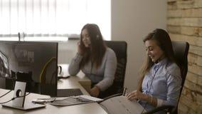 Девушки успешно работая в центре телефонного обслуживания Говорить к их клиентам сидя усмехаться сток-видео