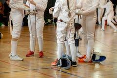 Девушки, участники в ограждая конкуренциях на шпагах стоят в центре ограждая залы стоковые фотографии rf