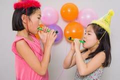 Девушки дуя noisemakers на вечеринке по случаю дня рождения Стоковые Фото