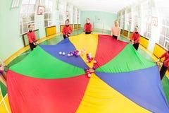 Девушки формируя круг вокруг парашюта радуги Стоковые Фото