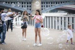 Девушки фотографируют пузыри мыла около южного берега Стоковые Изображения